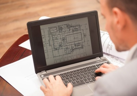 Close-up portrait of laptop with blueprints, architect sitting from behind working on architectural plan, interior shot